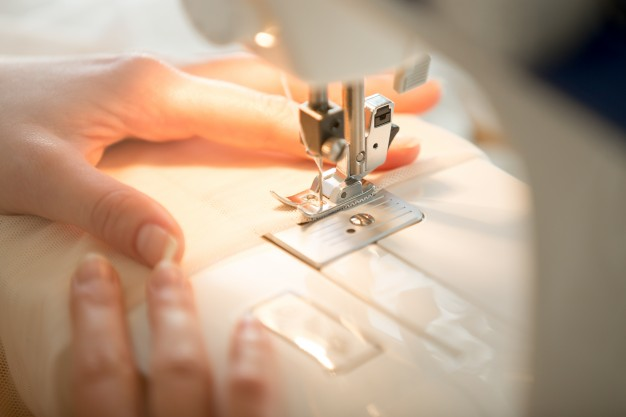 hands-at-sewing-machine_1163-2038